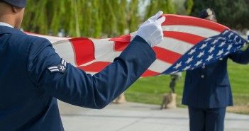 Airman 1st Class Stanley McDonald and Senior Airman Joshua McNair, defenders from the 366th Security Forces Squadron, fold the American Flag during Peace Officers Memorial Day retreat ceremony at Mountain Home Air Force Base, Idaho, May 15, 2014. President John F. Kennedy designated May 15th as Peace Officers Memorial Day and the week in which it falls as Police Week. (Photo Credit: U.S. Air Force photo by Staff Sgt. Roy Lynch III/RELEASED.)